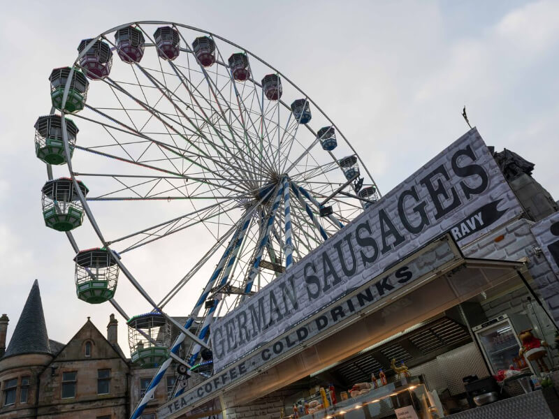 Festival Wheel against a grey sky with German sausage stand in front