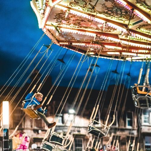 Child on wave swinger ride at night